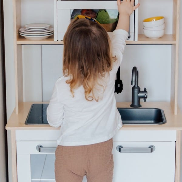 expressive language activities-imaginative play-young girl playing in her pretend kitchen