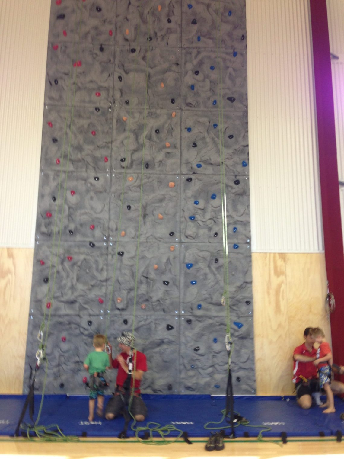 An Indoor Climbing Wall with 2 kids ready to climb