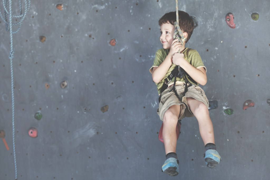 happy student climbing on an indoor wall