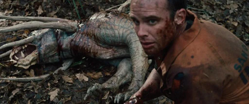 A bloody Walton Goggins in front of a fresh predator hound corpse as seen in Predators 2010.