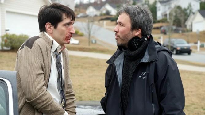 David Dastmalchian with bloody makeup speaks to Denis Villeneuve on the set of Prisoners.