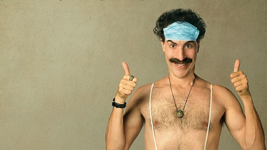 Sacha Baron Cohen as Borat comically wears a mask over his forehead while giving two thumbs up.