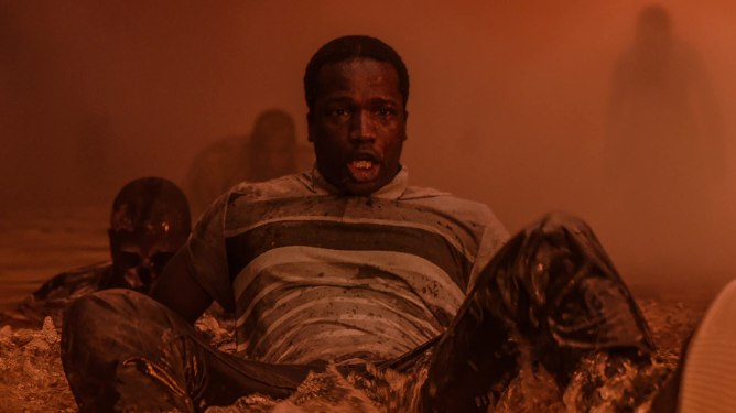 Sope Disiru drowns in an orange nightmare filled with other zombie refugees as seen in His House.