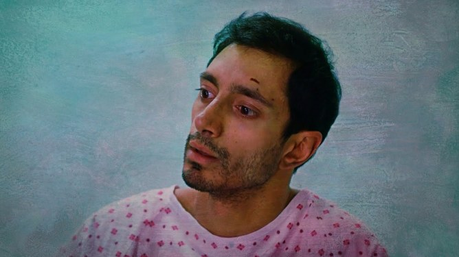 Riz Ahmed sits with a pink hospital scrub as seen in Mogul Mowgli.