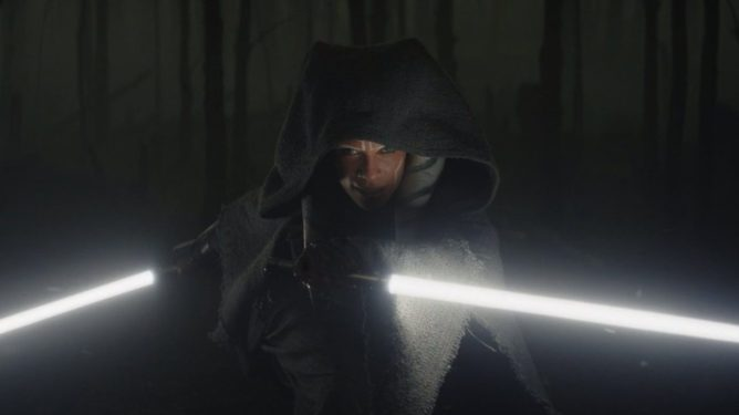 Rosario Dawson prepares to fight in a dark forest with her two bright white lightsabers as seen in Chapter 13 of The Mandalorian.