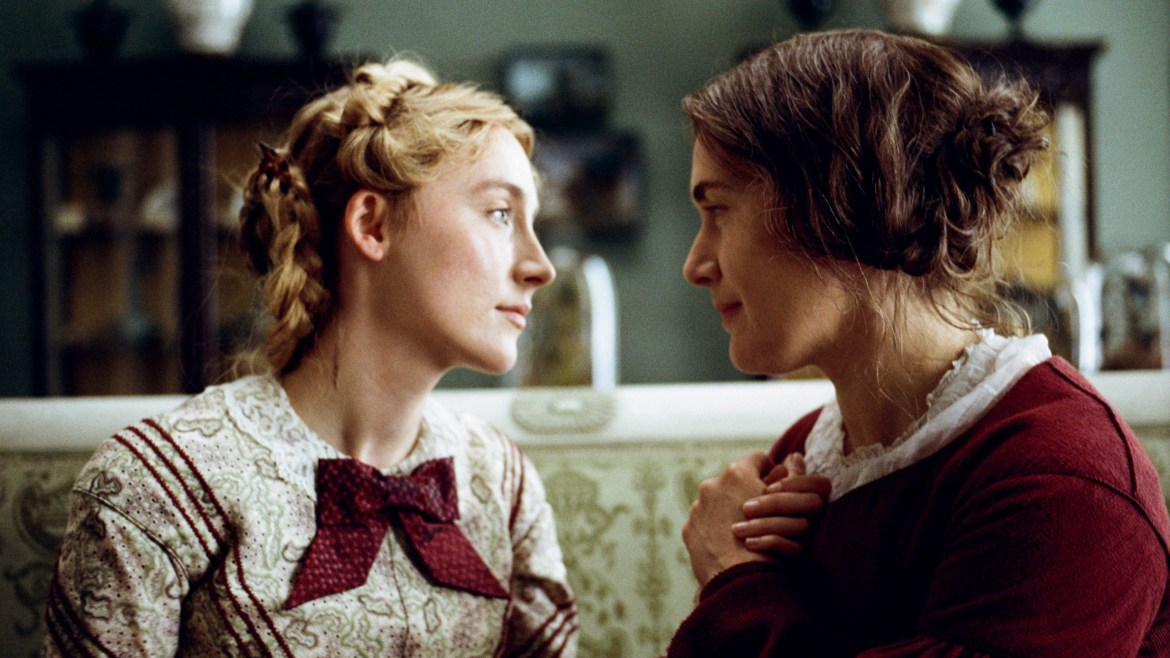 Kate Winslet and Saoirse Ronan hold hands together closely while both wearing passionate red clothing as seen in Ammonite.