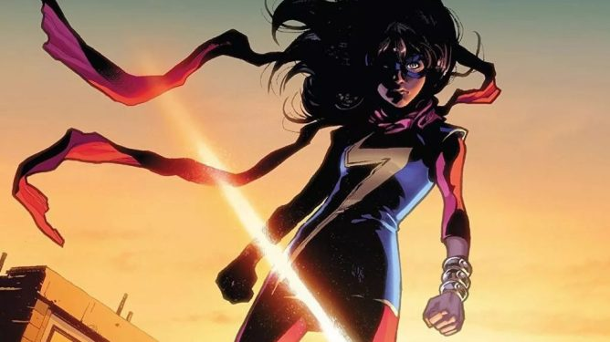 Kamala Khan stands on top of a building as her wind blows in the air behind a sunset as seen in Marvel Comics.