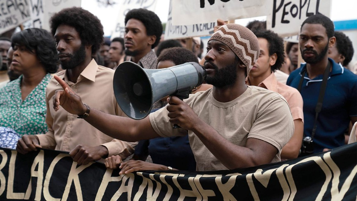 Malachi Kirby leads the Mangrove protests with a megaphone as seen in Steve McQueen's Small Axe anthology.