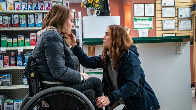 Sarah Paulson reaches down to Kiera Allen sitting in her wheelchair in a pharmacy as seen in Run.