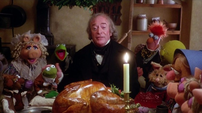 Michael Caine as Scrooge happily sharing a meal with the Muppets in The Muppet Christmas Carol.