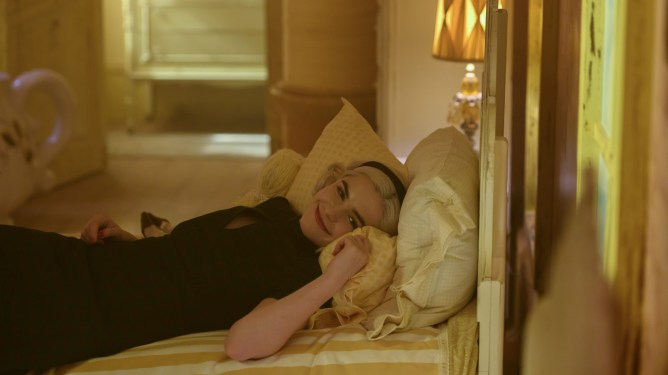 Kiernan Shipka as Sabrina the teenage witch laying down in a room covered in yellow and golden colors as seen in season 4 of The Chilling Adventures of Sabrina.