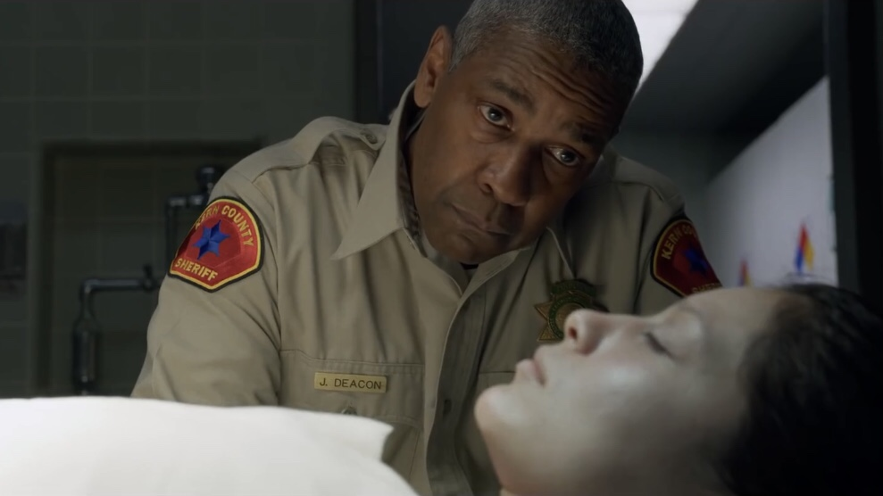 Denzel Washington in a Sheriff's uniform examines a corpse in a morgue as seen in The Little Things coming to HBO Max in January.