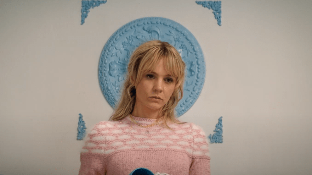 Carey Mulligan wearing a pink sweater against a white backdrop with blue decorations as seen in Promising Young Woman.