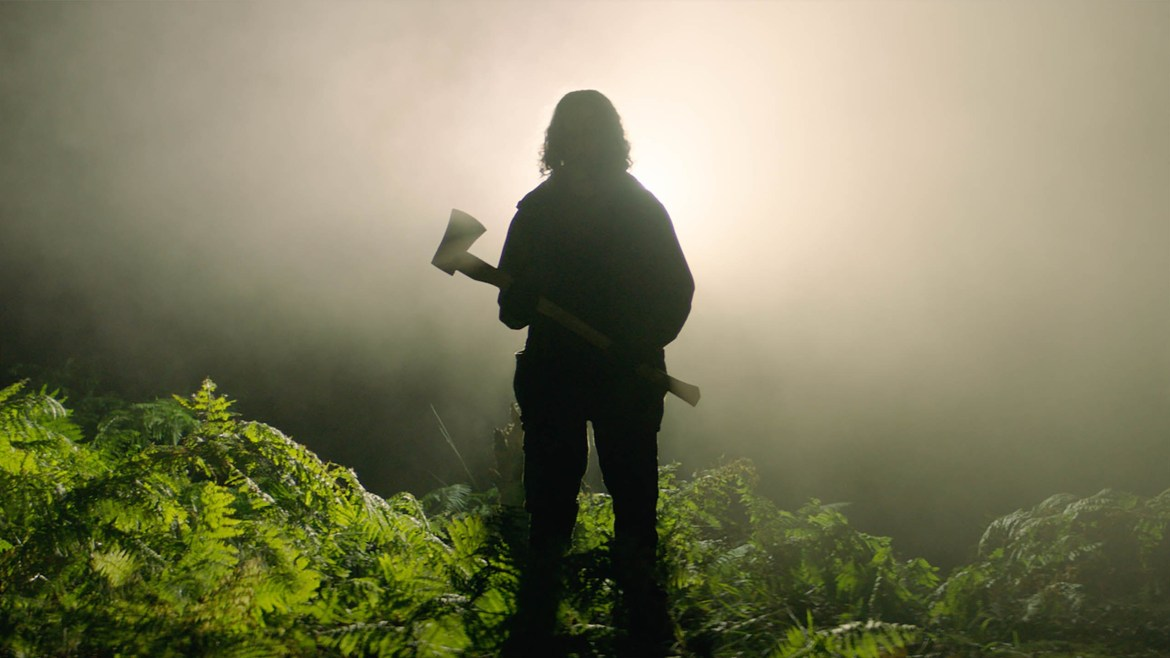The silhoutte of a man holding an axe in the foggy forest as seen in the Sundance 2021 selection In the Earth, directed by Ben Wheatley.