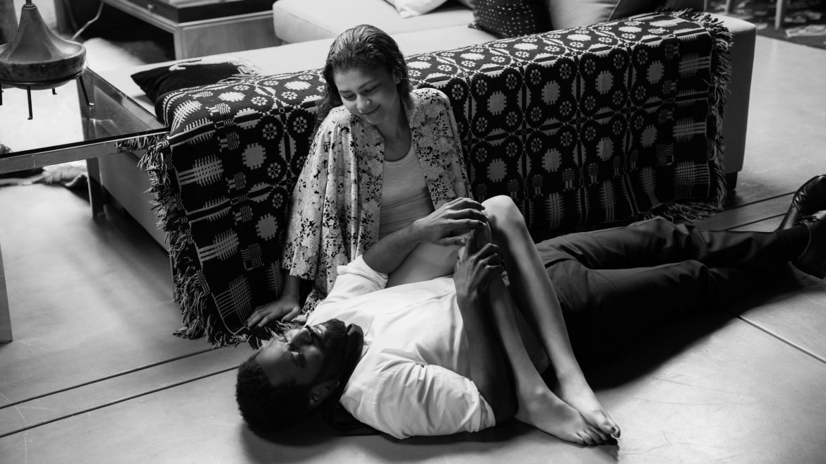 Zendaya and John David Washington sit carelessly on the floor together in their modern living room as seen in the black-and-white film Malcolm & Marie.