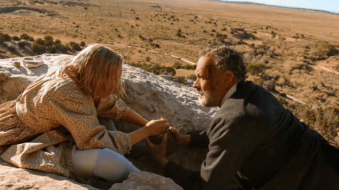 Tom Hanks and Helena Zengel hold each other on top of a large rocky hill overlooking a clear valley as seen in News of the World.