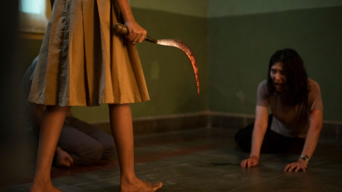 A woman looks in terror as someone in a dress approaches her with a bloody hook blade as seen in The Queen of Black Magic.