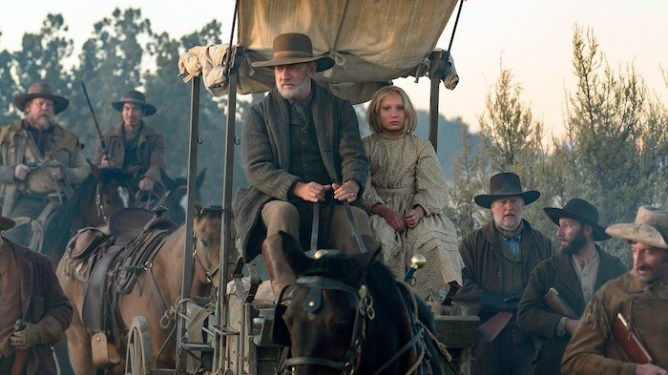 Tom Hanks and Helena Zengel ride in a horse wagon surrounded by armored guards on horses as seen in News of the World.