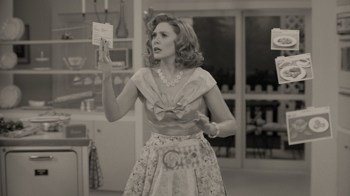 Elizabeth Olsen as Wanda Maximoff struggles to cook dinner with her magic powers in a 50s inspired black and white setting as seen in WandaVision.