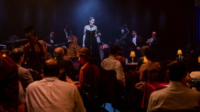 Andra Day as Billie Holiday singing in a dark and packed Jazz club as seen in The United States Vs. Billie Holiday.