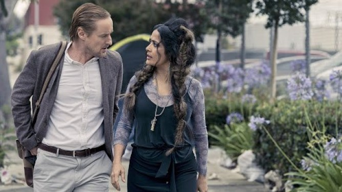 Owen Wilson and Salma Hayek having an intimate conversation by some flowers as seen in Bliss on Prime Video.
