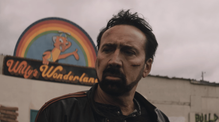 Nicolas Cage as the Janitor with battle scars standing outside of Willy's Wonderland as seen in the film directed by Kevin Lewis.