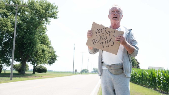 Udo Kier holding a free beauty tips sign on the side of the road as seen in the SXSW film Swan Song.