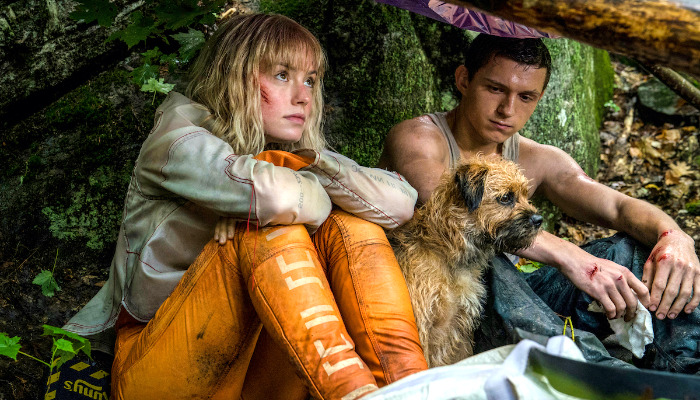Daisy Ridley, Tom Holland, and their small dog resting under a forest tree as seen in Chaos Walking.