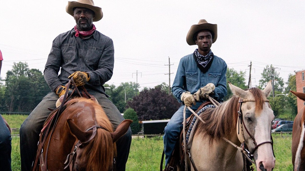 Idris Elba and Caleb McLaughlin riding horses in cowboy attire as seen in Concrete Cowboy directed by Ricky Staub.