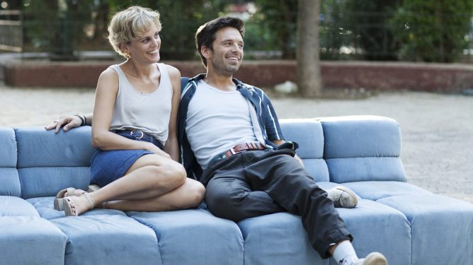 Denise Gough and Sebastian Stan sitting together in Greece as seen in the new romantic drama Monday.