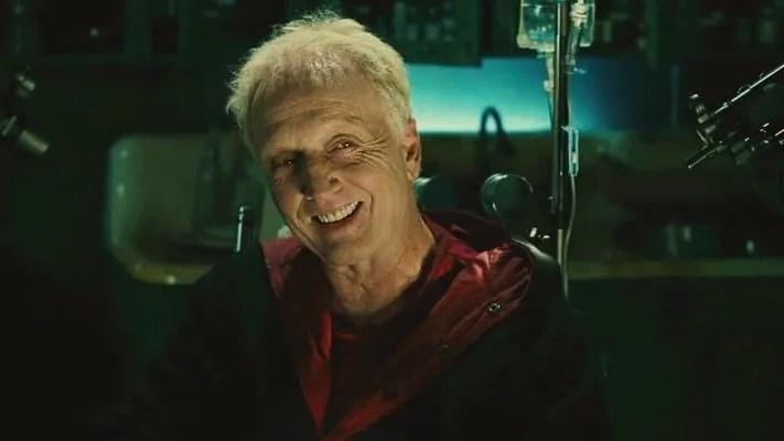 Tobin Bell as John Kramer aka Jigsaw smirking with guns up to his face as seen in Saw II.