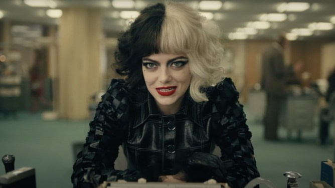 Emma Stone as Cruella sitting at a desk in a black leather outfit as seen in the new Disney live-action film.