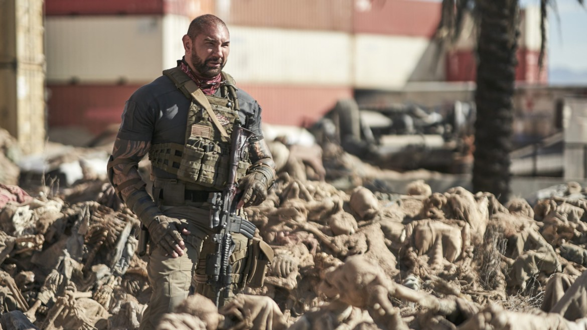 Dave Bautista in a mercenary uniform standing in a sea of zombie corpses as seen in the new Netflix film Army of the Dead directed by Zack Snyder.