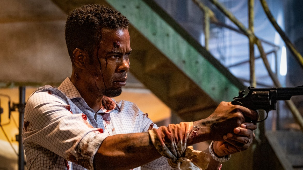 Chris Rock bloodied and injured holding up a gun as seen in the new horror film Spiral: From the Book of Saw.