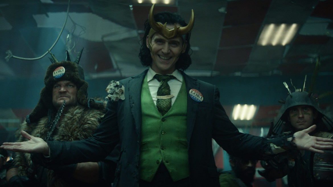 TomHiddleston as Loki wearing a button that says Loki for President next to ancient warriors as seen in the new Disney+ Marvel series Loki produced by Kevin Feige.