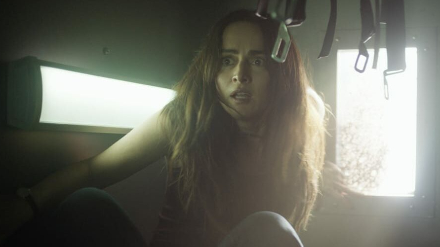 Ana de la Reguera stuck inside an upside police van as seen in the fifth and final Purge sequel from Blumhouse, THE FOREVER PURGE.