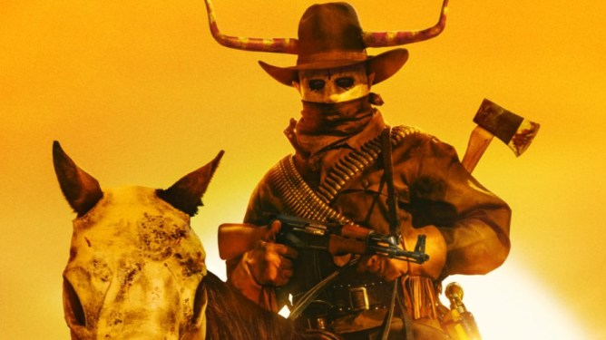 A masked cowboy purger with an axe and machine gun riding a masked skull horse as seen in THE FOREVER PURGE produced by JASON BLUM.