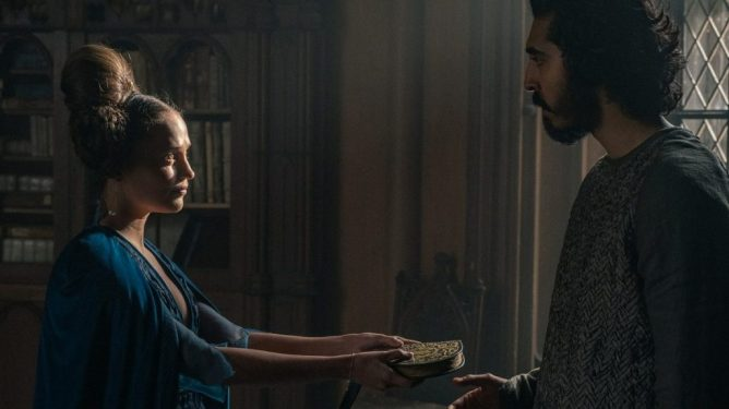 Alicia Vikander and Dev Patel share an intimate moment as seen in the new A24 film THE GREEN KNIGHT directed by David Lowery.