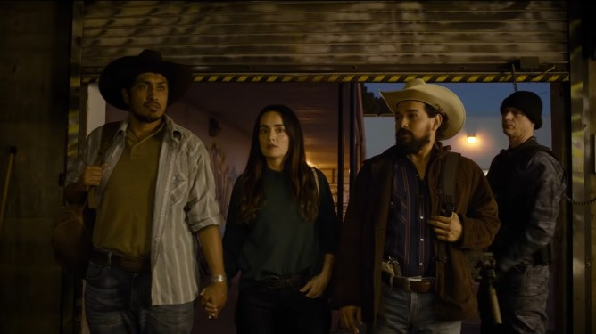 Ana de la Reguera and Tenoch Huerta entering a safety house on Purge night as seen in the new sequel, THE FOREVER PURGE.