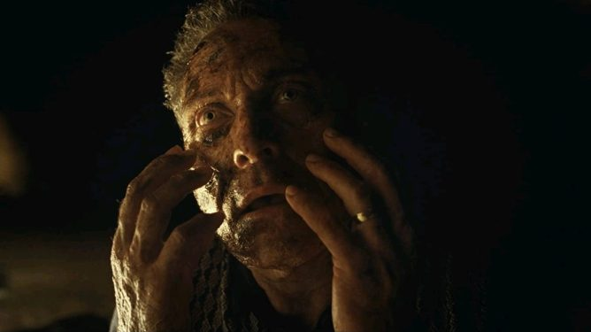 Rufus Sewell feeling his rapidly aging face on a dark beach as seen in the new  M. Night Shyamalan horror thriller OLD.
