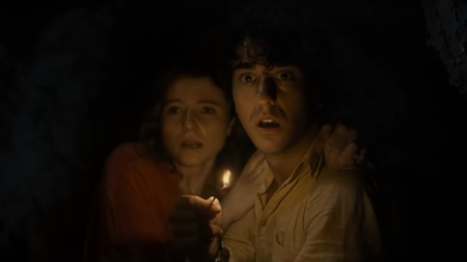 Alex Wolff and Thomasin McKenzie holding each other in fear inside a dark cave as Alex raises one bright lit match as seen in the new M. Night Shyamalan horror thriller OLD.
