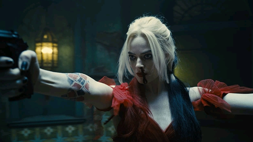 Margot Robbie as Harley Quinn in a ripped red dress going gun crazy as seen in The Suicide Squad, coming to HBO Max in August.