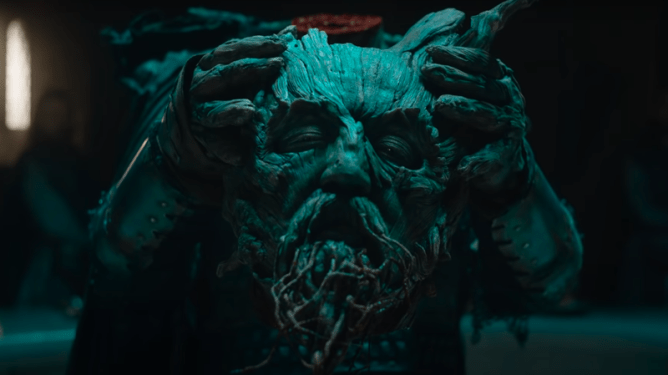 The Green Knight himself, a being made out of tree bark and roots, holds his own decapitated head inside Camelot as seen in the new A24 film THE GREEN KNIGHT directed by David Lowery.