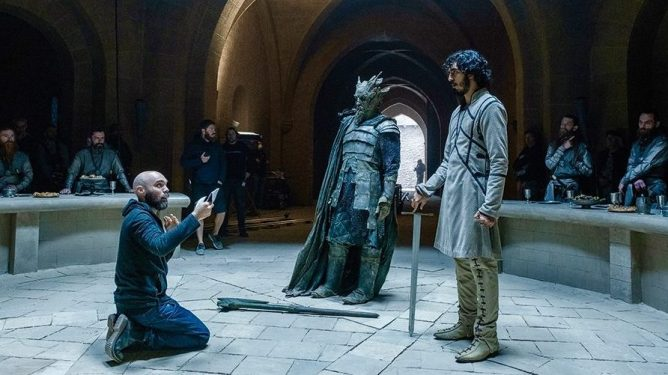 Director David Lowery stages a scene with Ralph Ineson in full Green Knight costume and makeup and Dav Patel as Sir Gawain on the set of the latest A24 film.