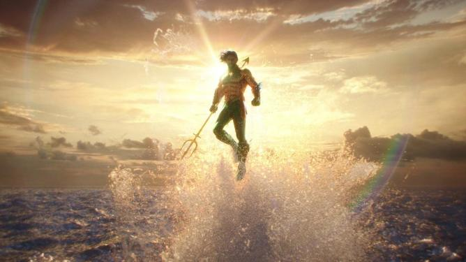 Jason Momoa as Aquaman rises above the ocean waters holding his trident against a sunset as seen in AQUAMAN, coming in at number 5 in our DCEU ranking from worst to best.