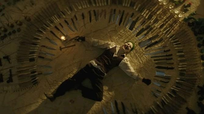 Jared Leto as the Joker laying down in a circle of sharp knives and assorted guns and weapons as seen in SUICIDE SQUAD, ranking dead last on our DCEU ranking.