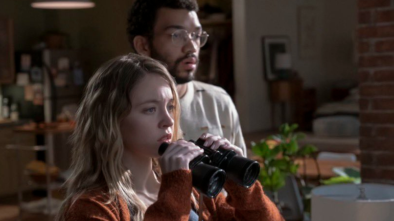 Sydney Sweeney and Justice Smith spy on their neighbors using binoculars as seen in THE VOYEURS on Prime Video.
