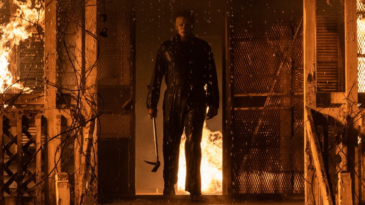 Michael Myers walks through the flames of a burning house holding a large crowbar as seen in HALLOWEEN KILLS directed by David Gordon Green.
