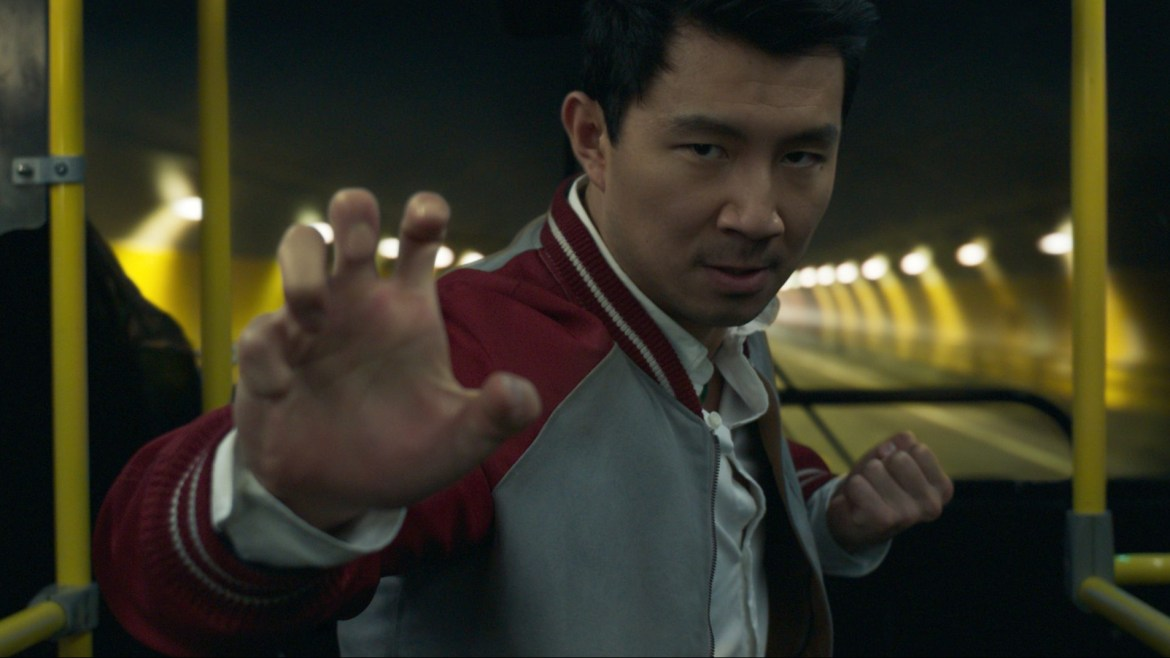 Simu Liu as Shang-Chi in the middle of a Kung-Fu pose on a bus as it enters a yellow tunnel as seen in SHANG-CHI AND THE LEGEND OF THE TEN RINGS.
