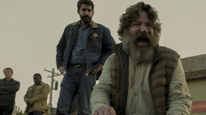 Rahul Kohli as Sherrif Hassan tending to a distraught, yelling townsperson in MIDNIGHT MASS directed by Mike Flanagan on Netflix.